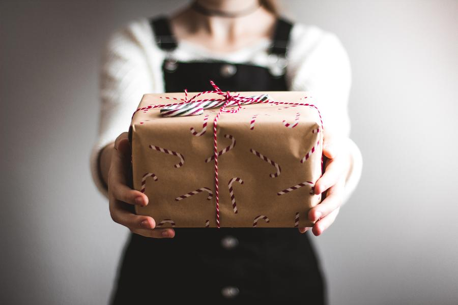 woman indoors, giving gift