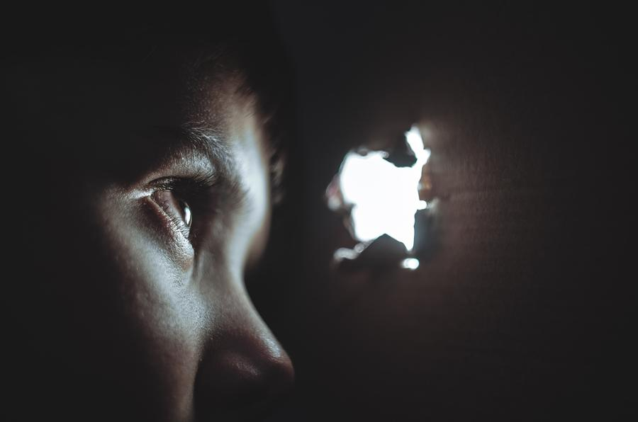 woman looking outside through a torn hole