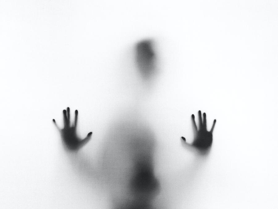 person, outside blurry window, hands, head, black and white